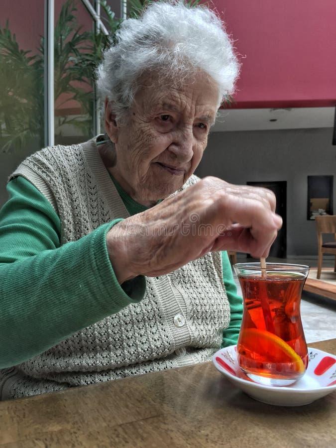 De hogere vrouw beweegt een glas thee op lijst royalty-vrije stock afbeeldingen