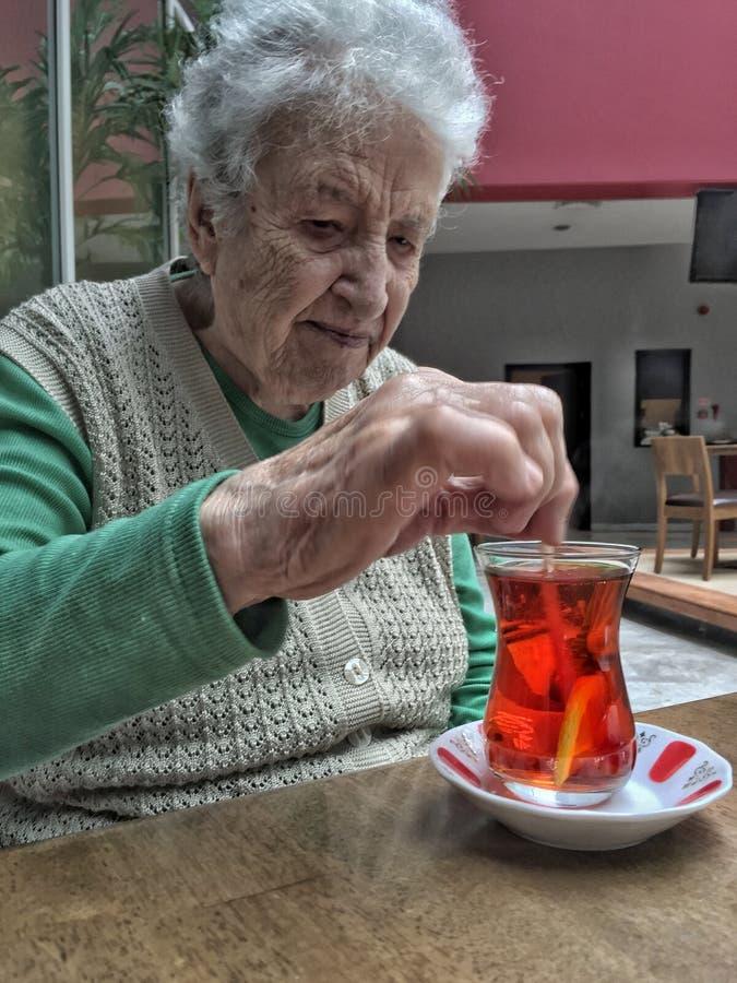 De hogere vrouw beweegt een glas thee op lijst stock afbeelding