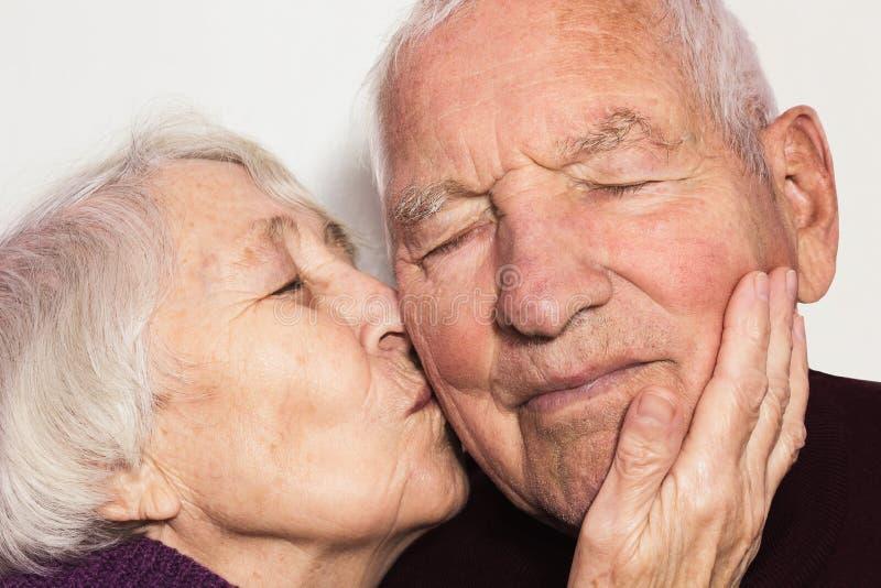 De hogere vrouw die de oude mens kussen stock afbeeldingen