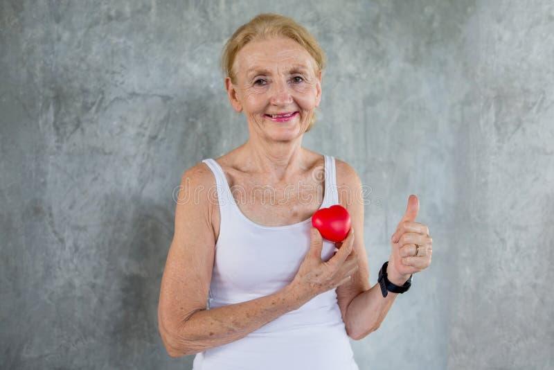 De hogere vrouw die rood hartstuk speelgoed houden en toont Duimen in geschiktheidsgymnastiek het oude dame uitoefenen Oude vrouw stock foto