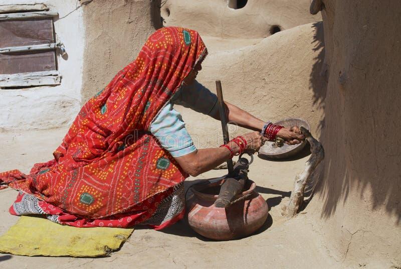 De hogere vrouw die traditionele kleding dragen doet huishoudelijk werk in een binnenplaats van een huis in Jamba, India stock foto