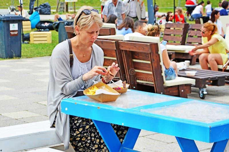 De hogere vrouw eet straatvoedsel stock afbeelding