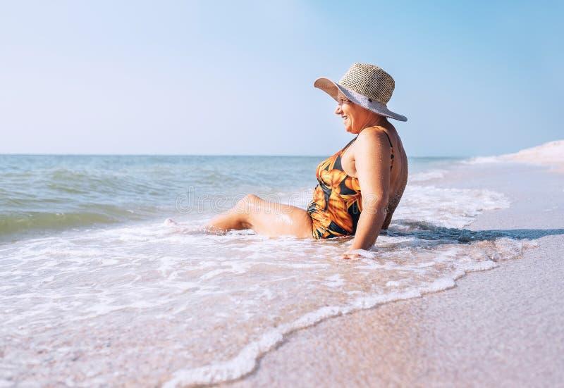 De hogere vrouw geniet van de zitting van de strandvakantie op overzeese surfline royalty-vrije stock foto