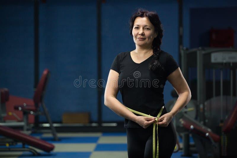 De hogere vrouw in de gymnastiek meet de taille met een metende band Close-up De ruimte van het exemplaar stock foto