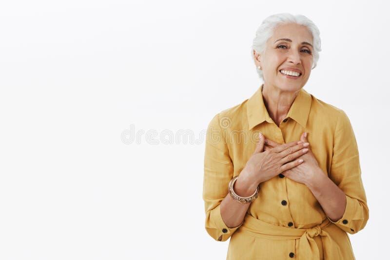 De hogere vrouw houdt krijgend complimenten kijkend vers en mooi Opgetogen gelukkige charmante oude dame met wit binnen haar stock afbeelding
