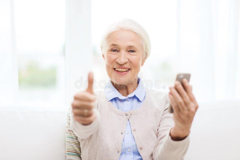 De hogere vrouw met smartphone het tonen beduimelt omhoog stock afbeeldingen