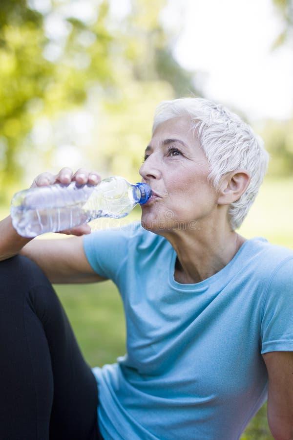 De hogere vrouw rust en drinkt water na training stock foto
