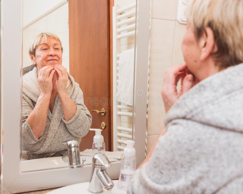 De hogere vrouw wat betreft haar zachte gezichtshuid en masseert, thuis kijkend in spiegel stock fotografie
