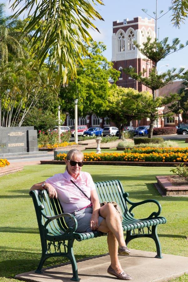 De hogere vrouw zat in Buss-park met de vroegere van de de kerk nu Zevende Dag van Presyterian St Andrews Adventistenkerk op de a royalty-vrije stock foto's