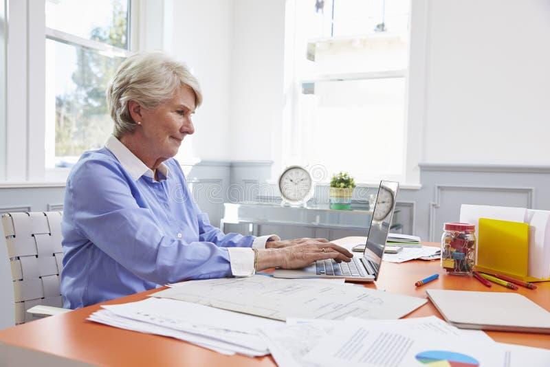 De hogere Vrouw zit bij Bureau en werkt aan Laptop in Huisbureau stock afbeeldingen