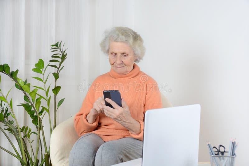 De hogere vrouw zit en leest het recentste nieuws op haar telefoon stock foto's