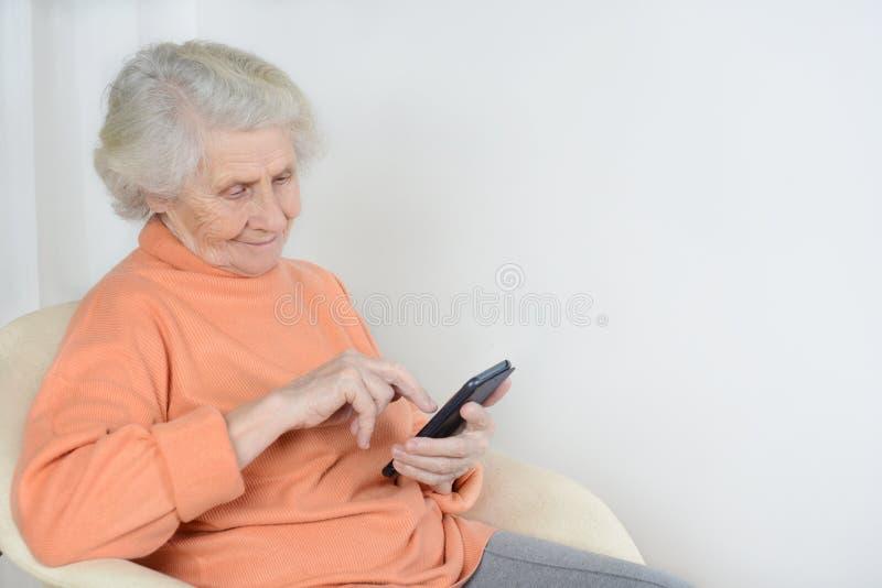 De hogere vrouw zit en leest het recentste nieuws op haar telefoon stock afbeeldingen