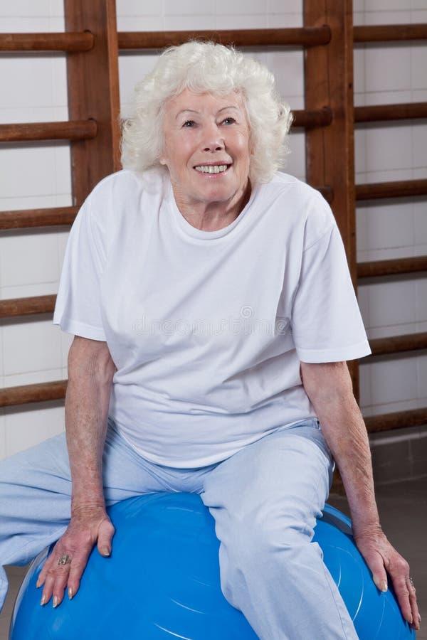 De hogere Vrouw zit op een Fitball stock foto