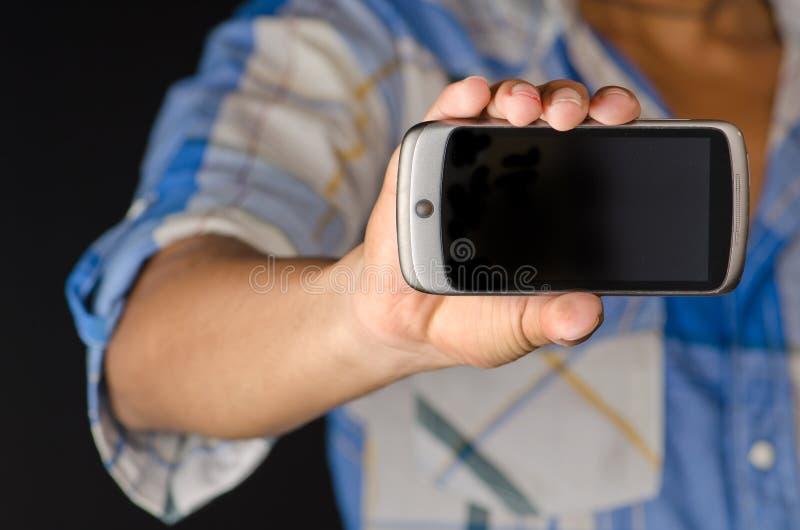 De holding die van de hand het spelen androïde slimme telefoon met behulp van stock afbeelding