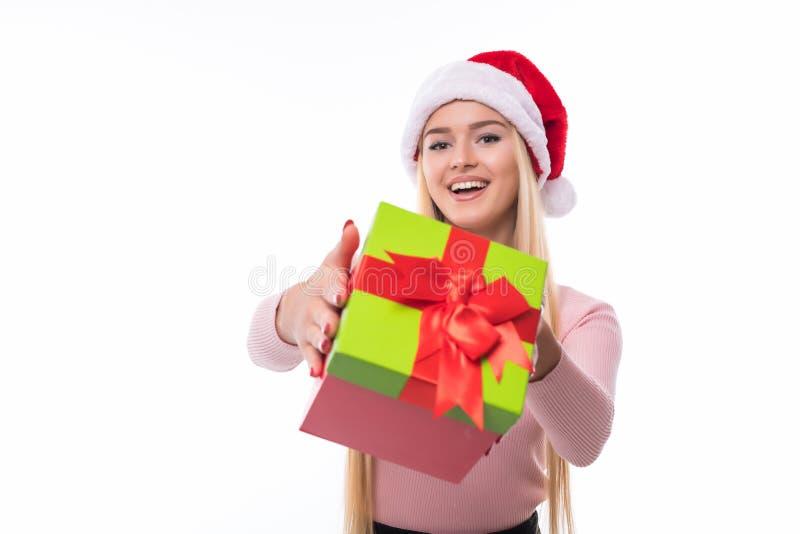De holding die van de Kerstmisvrouw gift het opgewekte richten geven Gelukkige glimlachende vrouw in santahoed die u een heden ge royalty-vrije stock afbeelding