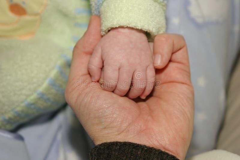De holding-Handen van vader-en-zoon in een Akte van Liefde stock fotografie