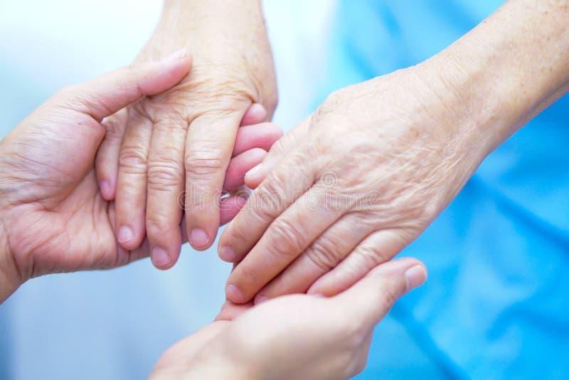 De holding overhandigt Aziatische oudste of de bejaarde oude patiënt van de damevrouw met liefde, zorg, moedigt en empathie bij h royalty-vrije stock foto