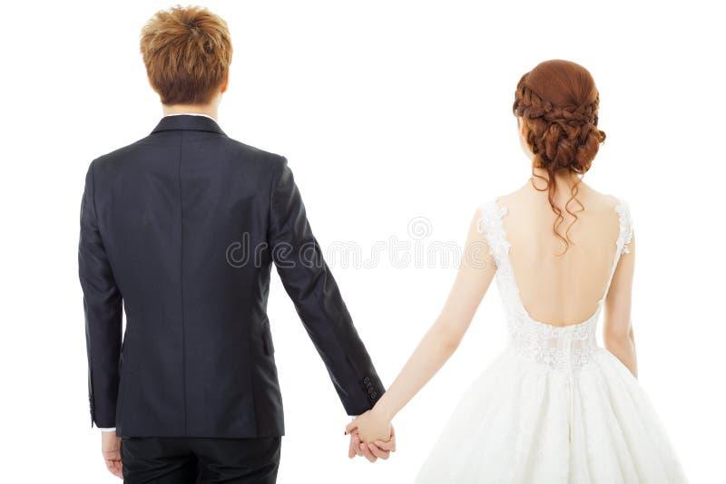 de holding overhandigt bruid en bruidegom op wit wordt geïsoleerd dat royalty-vrije stock foto's