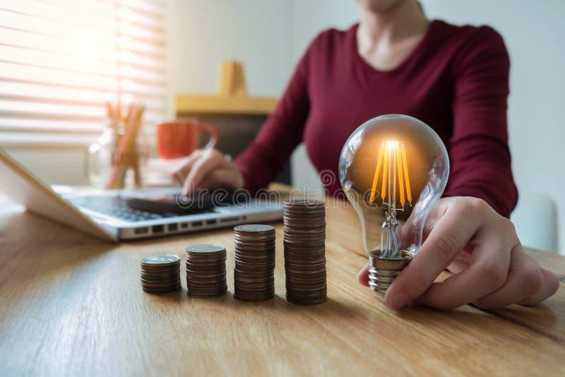 de holding van de bedrijfsvrouwenhand lightbulb met muntstukkenstapel op bureau stock foto's