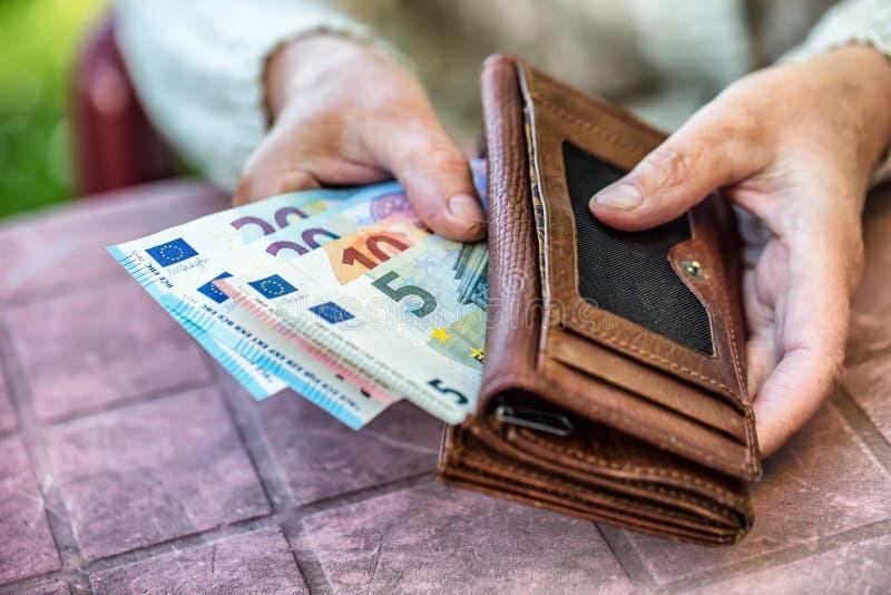 De holding van de gepensioneerdevrouw in handenportefeuille zonder geld stock fotografie