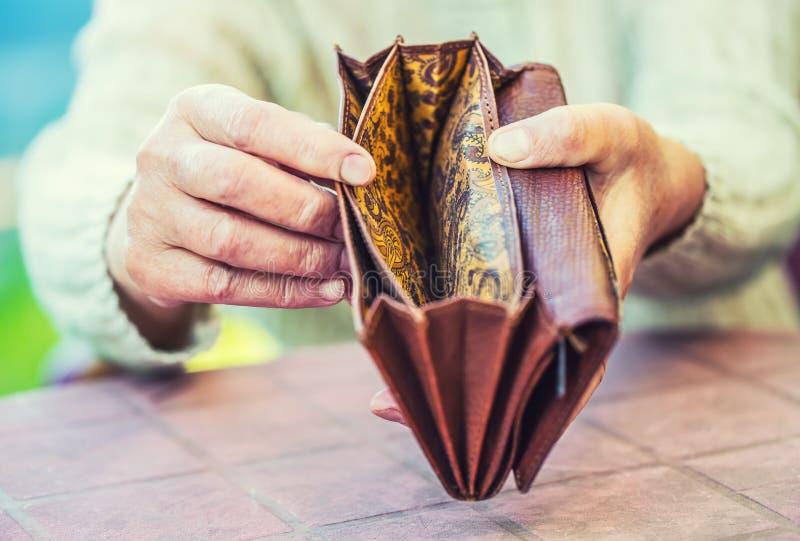 De holding van de gepensioneerdevrouw overhandigt portefeuille zonder geld royalty-vrije stock fotografie