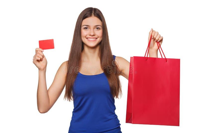 De holding van de glimlach mooie gelukkige vrouw het winkelen zak en het tonen van lege die creditcard, verkoop, op witte achterg royalty-vrije stock afbeeldingen