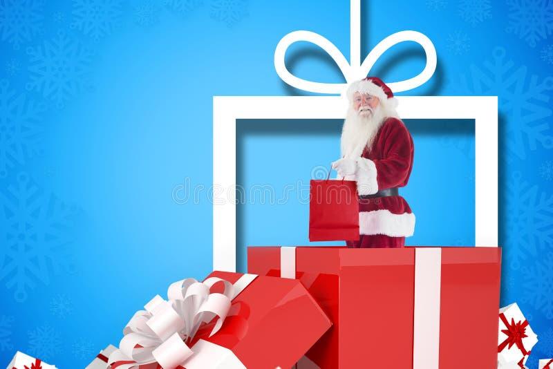 De holding van de Kerstman het winkelen zak terwijl status binnen giftdoos royalty-vrije stock foto
