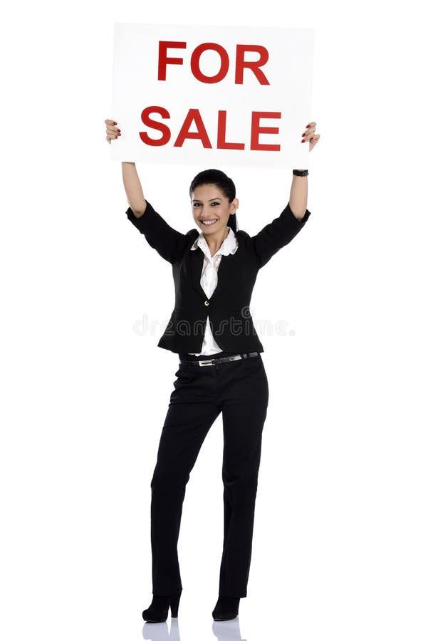 De holding van de onroerende goederenvrouw voor verkoopteken stock foto