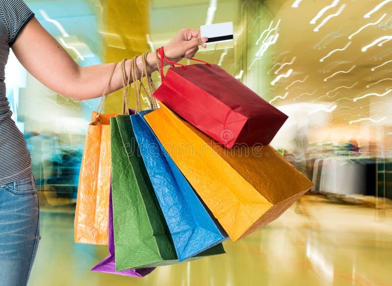De holding van de vrouw creditcard en het winkelen zakken stock afbeelding