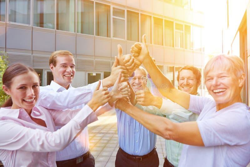 De holding van het bedrijfsmensenteam beduimelt omhoog royalty-vrije stock foto