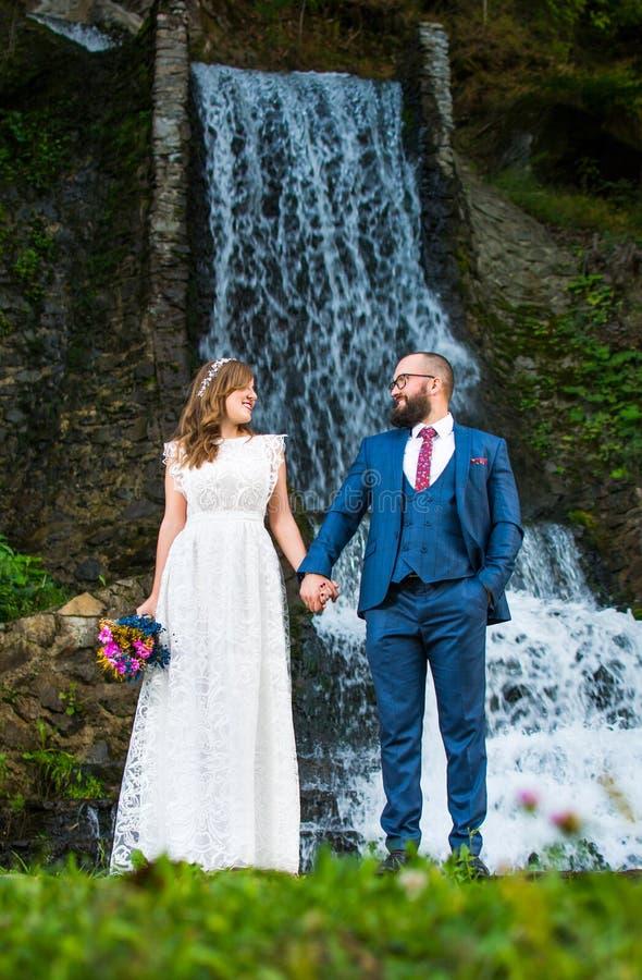 De holding van het huwelijkspaar dient voorzijde van een waterval in stock foto