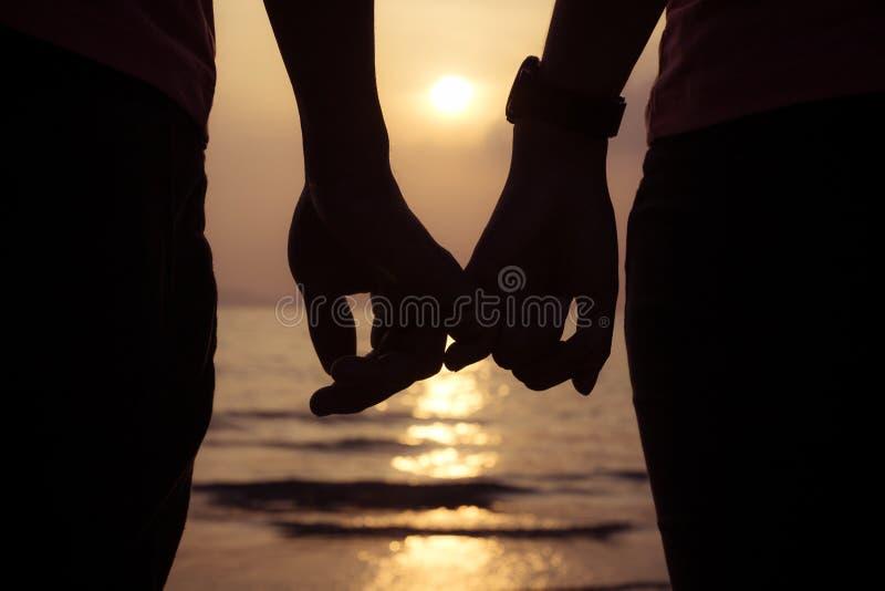 de holding van het liefdepaar overhandigt vingers bij zonsondergang op het strand stock afbeelding