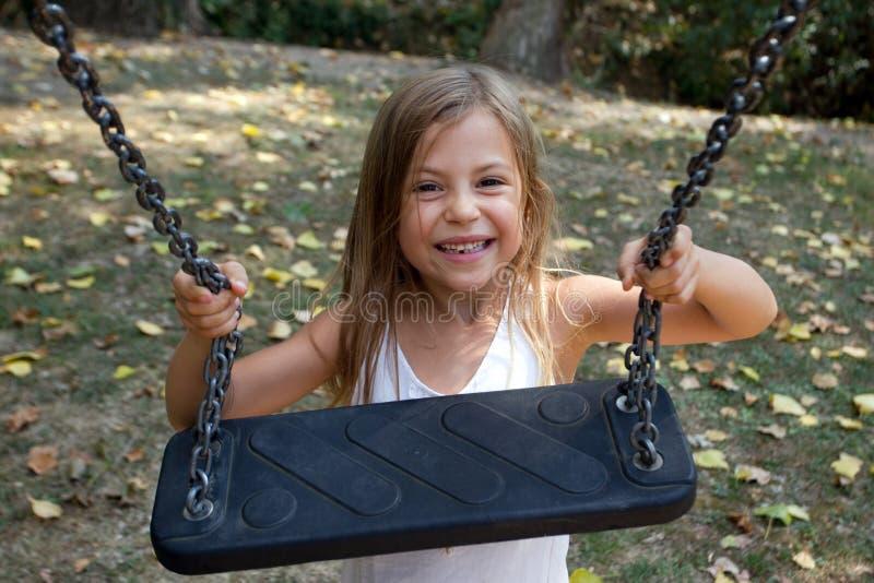 De holding van het meisje op schommeling royalty-vrije stock afbeeldingen