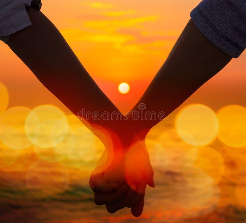 De Holding van het paar overhandigt op zee Zonsondergang stock foto's
