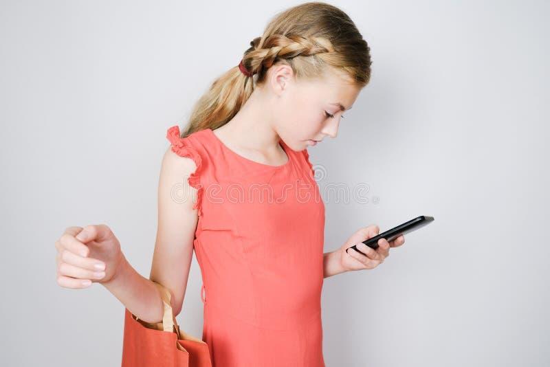 De holding van het tienermeisje het winkelen zak en het bekijken mobiele telefoon royalty-vrije stock foto