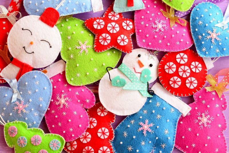 De holding van Kerstmis background Leuke gevoelde ornamenten voor Kerstmis Gevoelde Kerstbomen, sneeuwmannen, harten, sterren, vu royalty-vrije stock foto's