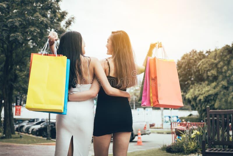 De holding van de twee tiener mooie Aziatische vrouw het winkelen zak bij shopp stock afbeelding