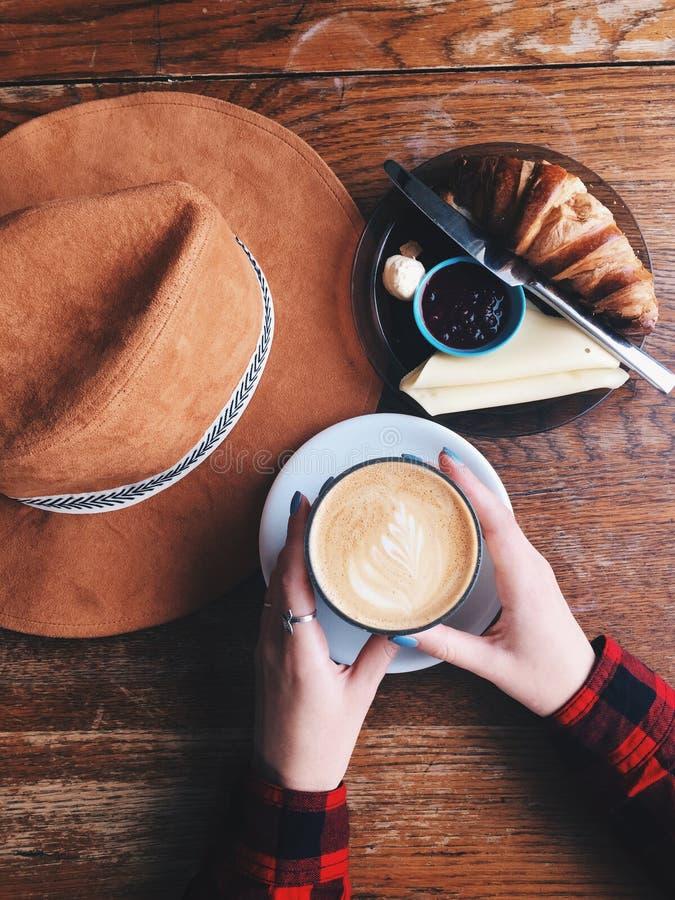De holding van de vrouwenhand een kop van koffie heerlijk dessert op houten lijst Uitstekend beeld Hoogste mening stock foto