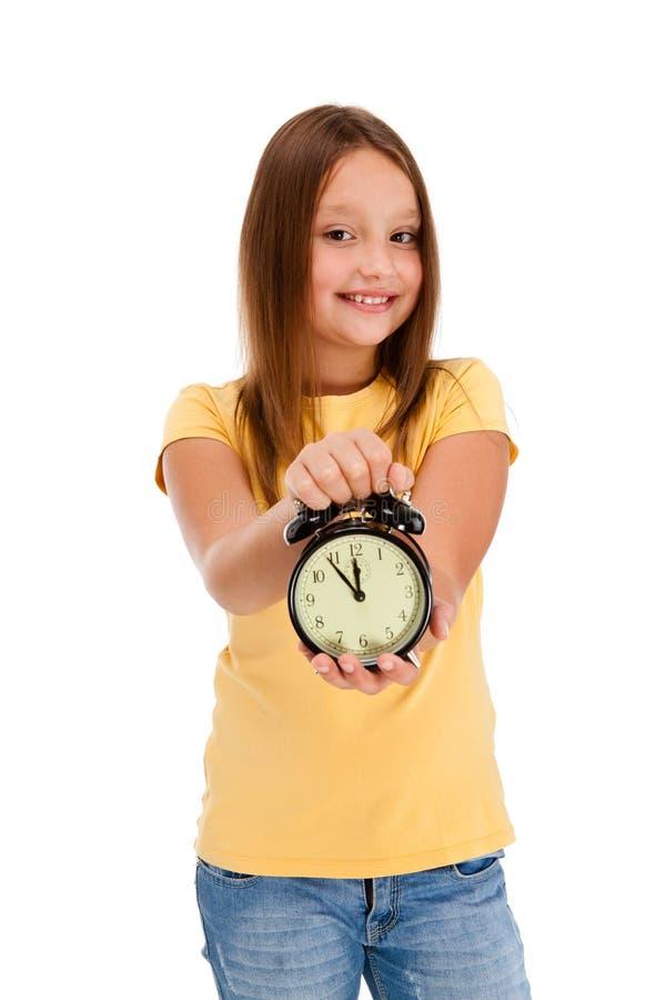 De holdings alarm-klok van het meisje die op wit wordt geïsoleerdu stock foto