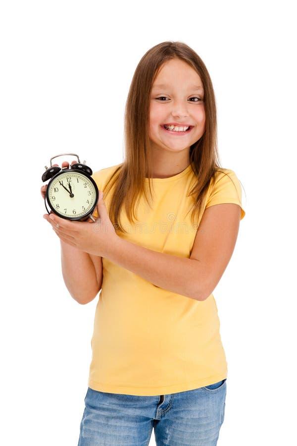 De holdings alarm-klok van het meisje die op wit wordt geïsoleerdw stock foto