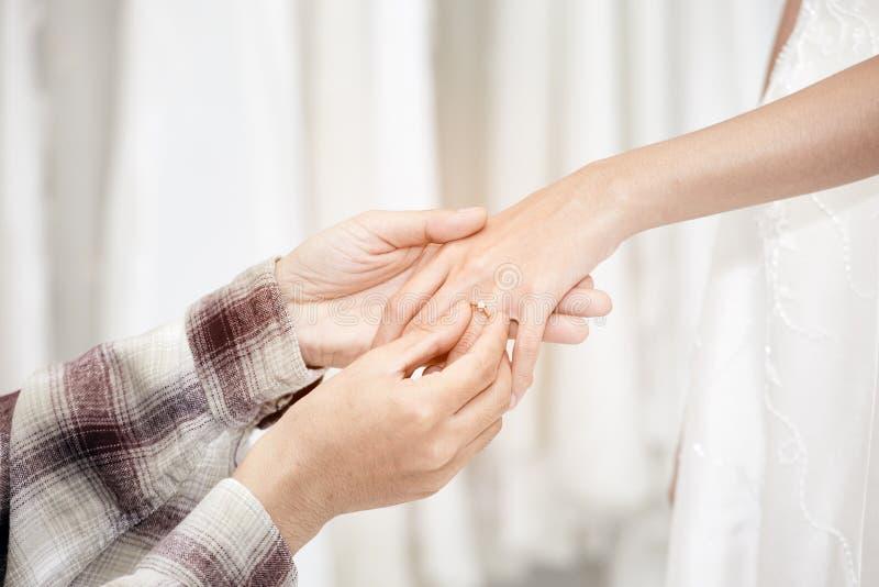 De de holdings bride's hand van de Groom'shand en draagt een trouwring op bride'sringvinger royalty-vrije stock foto