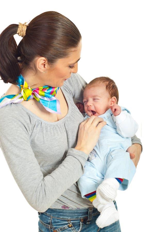 De holdings geeuwende baby van de moeder stock afbeeldingen
