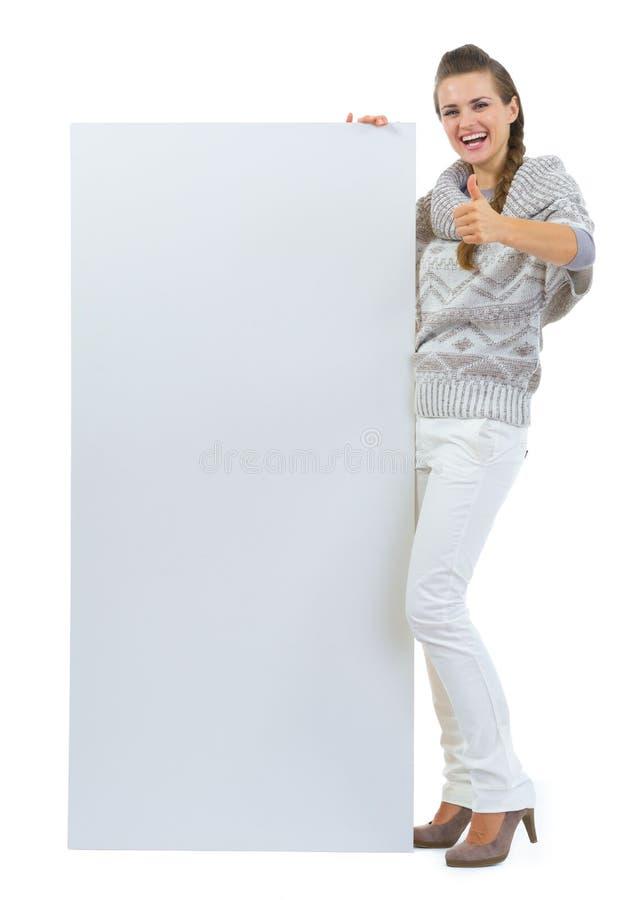 De holdings leeg aanplakbord van de vrouw en het tonen van duim stock foto