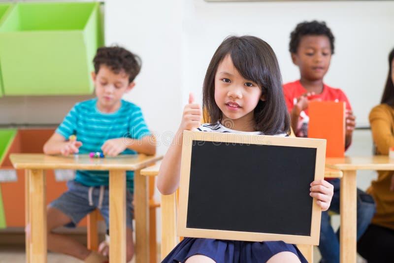 De holdings leeg bord van het jong geitjemeisje met diversiteitsvrienden en leraar bij achtergrond, Kleuterschoolkleuterschool, s stock foto's