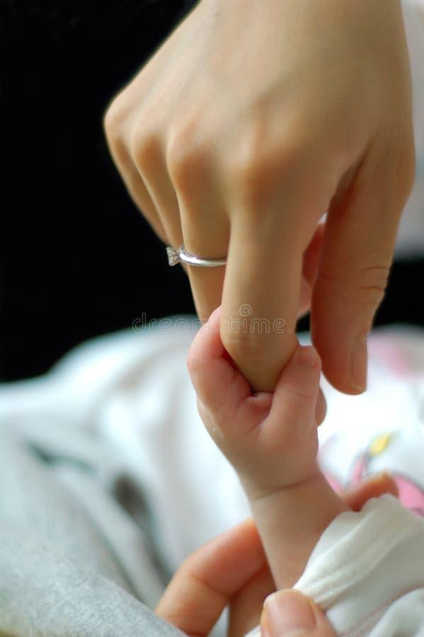 De holdings mum vinger van de baby stock afbeeldingen