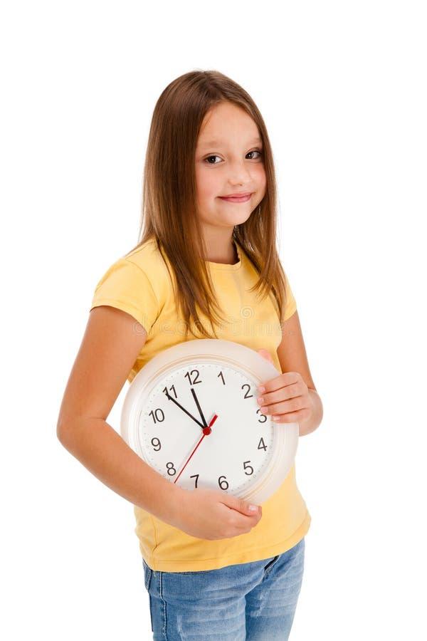 De holdings muur-klok van het meisje die op wit wordt geïsoleerdr royalty-vrije stock afbeelding
