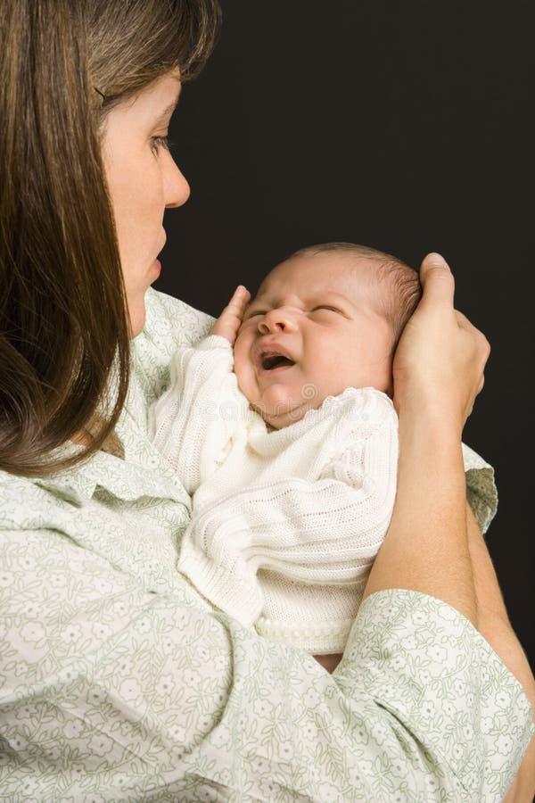 De holdings schreeuwende baby van de moeder. stock foto