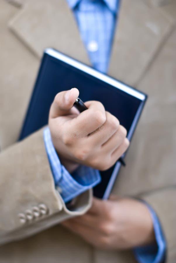 De holdingsagenda en pen van de manager op kantoor stock afbeeldingen