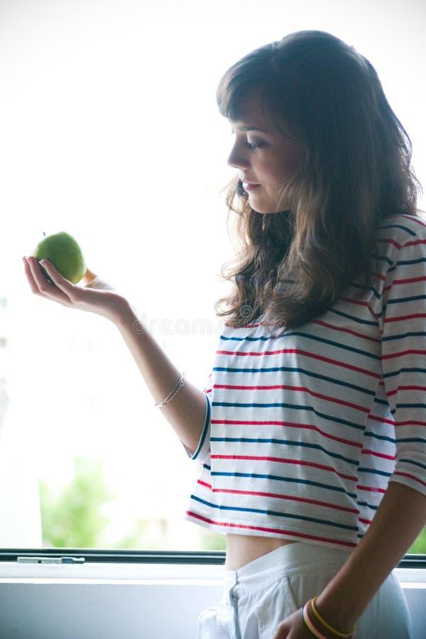 De holdingsappel van het meisje stock afbeelding