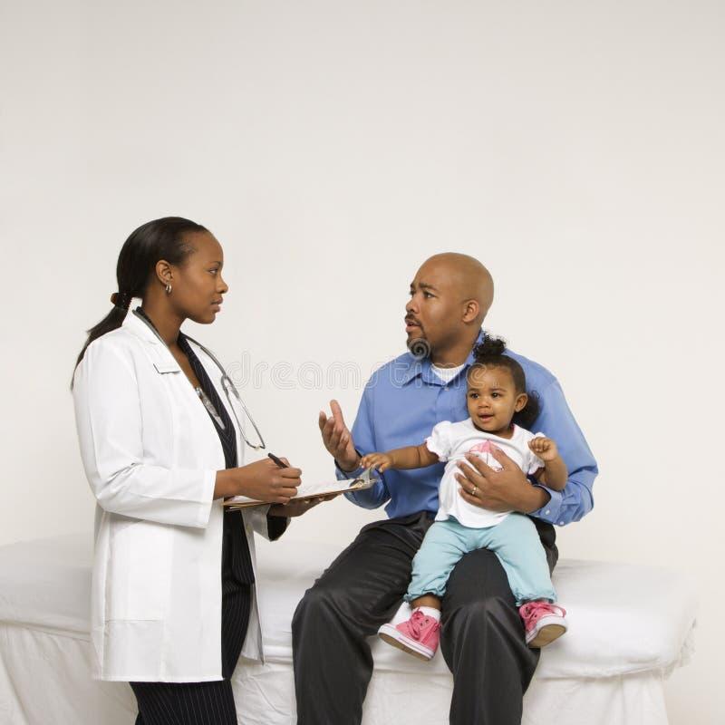 De holdingsbaby die van de vader aan pediater spreekt. stock foto